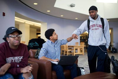 """Rozzie Caribs (center) greets his friend Calvin Stewart during a """"study jam"""" at the library at Southern Illinois University, Carbondale on April 10. Cribbs received a full-ride college scholarship through the Jordan Brand's Wings program."""